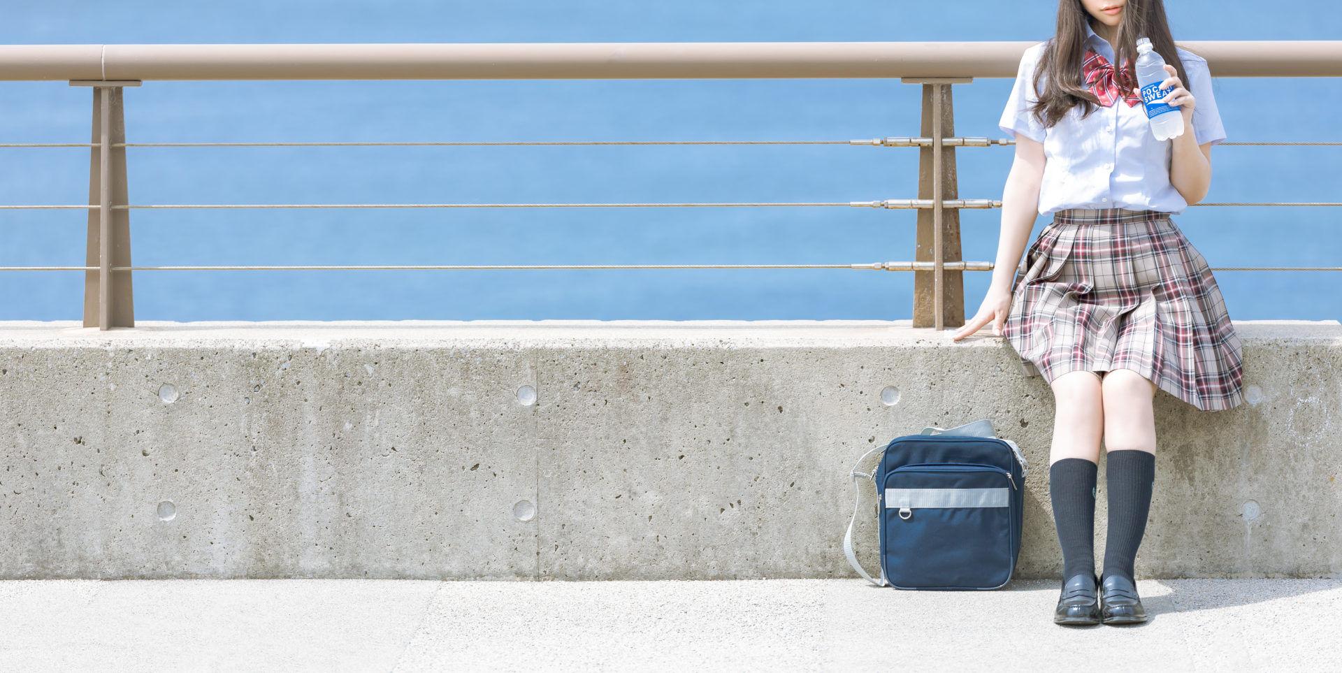 初夏にバスを待つ高校3年生
